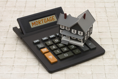 50184553 - home mortgage, a gray house and calculator on stone background with text mortgage