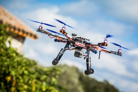 24303812 - professional carbon drone with gps and video camera making a ride.