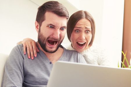 40300556 - indoor photo of amazed screaming couple looking at laptop