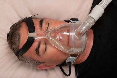 18229753 - man sleep with apnea and cpap machine