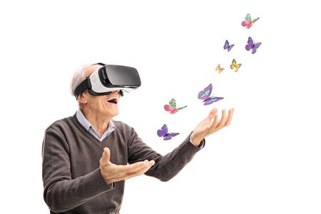 52866605 - joyful senior gentleman visualizing butterflies via vr headset isolated on white background